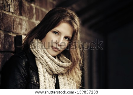 Teenage girl against a brick wall - stock photo