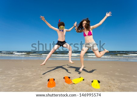 Teenage girl and boy jumping, running on beach - stock photo