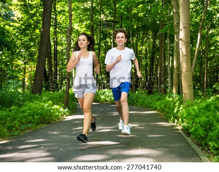 Teenage girl and boy running in park  - stock photo