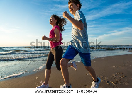 Teenage girl and boy running, jumping on beach  - stock photo