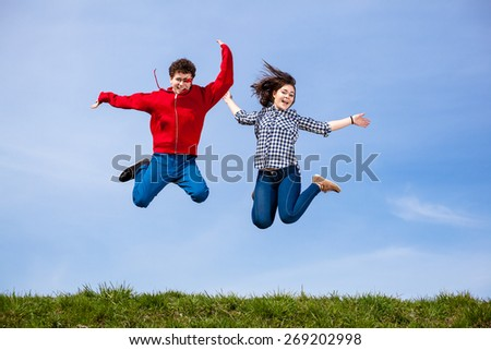 Teenage girl and boy running, jumping outdoor - stock photo