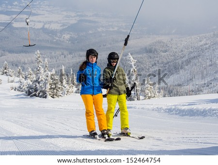 Teenage girl and boy skiing - stock photo