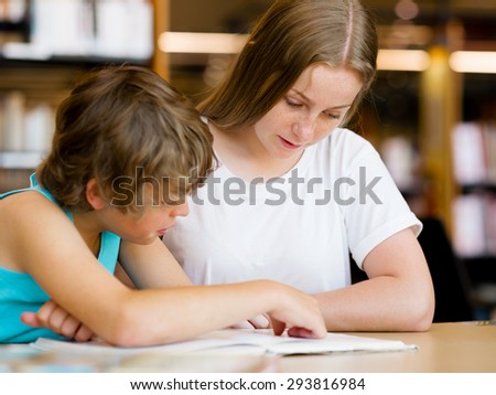 Teenage girl  and her brother with books studying in library - stock photo