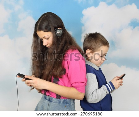Teenage girl and little boy with cell phones on cloudy blue sky background - stock photo