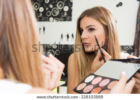Teenage girl applying makeup on eyes - stock photo
