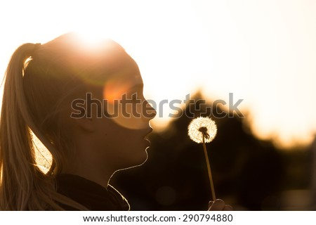teenage girl backlit by the sun holding a dandelion seed head preparing to blow on it. Copy space to the right top of image and plenty of lens flare - stock photo