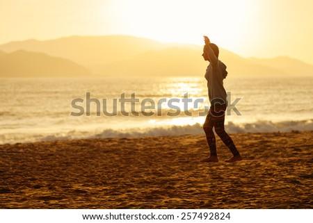 teenage girl balance slackline on the beach sunrise silhouette - stock photo