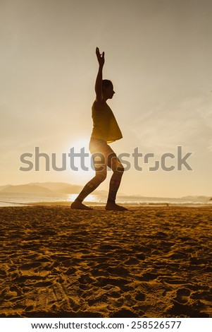 teenage girl  balancing on slackline  on the beach in sunrise silhoutte