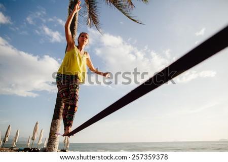 teenage girl  balancing on slackline with sky view on the beach - stock photo