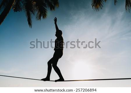 teenage girl  balancing on slackline with sky view on the beach silhouette - stock photo