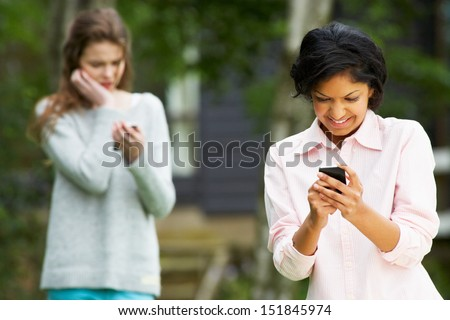 Teenage Girl Being Bullied By Text Message On Mobile Phone - stock photo