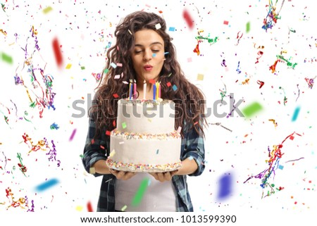 Teenage girl blowing candles on a birthday cake with confetti streamers flying around her isolated on white background