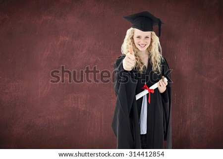 Teenage Girl Celebrating Graduation with thumbs up against desk - stock photo