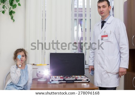 Teenage girl checks sight at the reception of an ophthalmologist - stock photo
