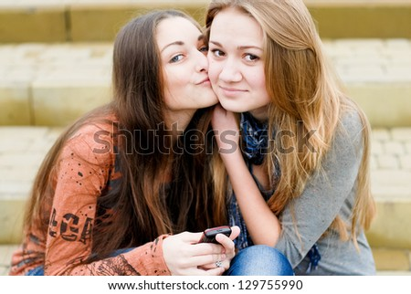 Teenage girl comforting her friend reading message - stock photo
