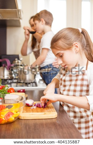 Teenage girl cooking together with her family in the kitchen. Caucasian girl cutting onion for salad Family cooking background