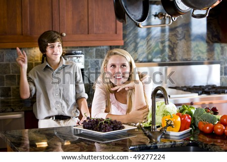 Teenage girl daydreaming in kitchen with brother in background teasing - stock photo