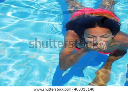 teenage girl diving in the blue transparent swimming pool underwater holding breath - stock photo