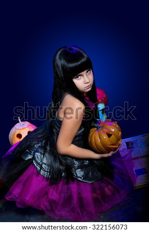 Teenage girl dressed as a witch with a lot of pumpkins. Studio photo.