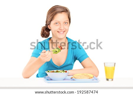 Teenage girl eating a toast and salad seated at a table isolated on white background