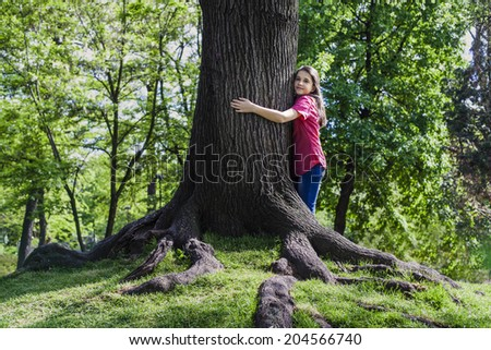 Teenage girl embracing  stem of a tree