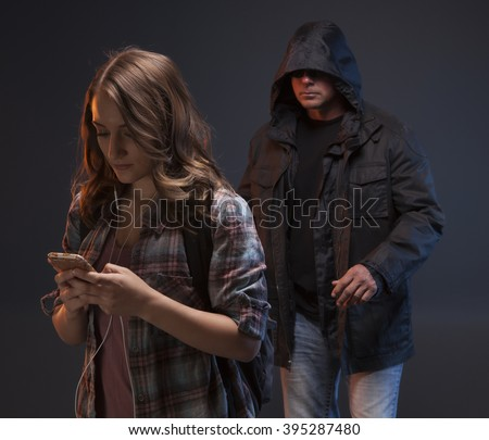 Teenage Girl gets attacked by a stranger. He sees her texting and walking. Teen girl does not know there is a scary man coming up behind her. - stock photo