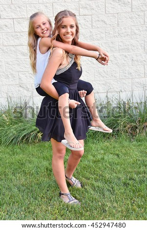 teenage girl giving a younger sister a piggyback ride - stock photo