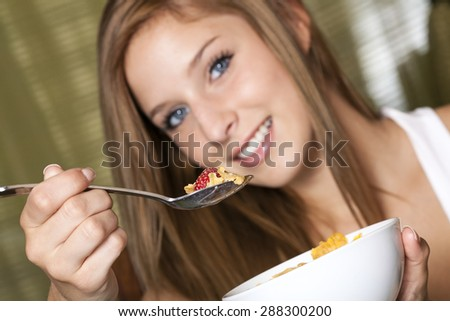 Teenage girl having breakfast - stock photo