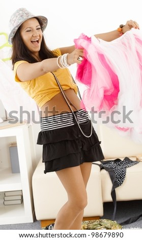 Teenage girl having fun at home, trying clothes, laughing. - stock photo