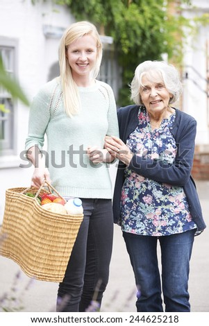 Teenage Girl Helping Senior Woman To Carry Shopping - stock photo