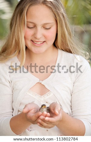 Teenage girl holding a baby bird in her hands while sitting at a home garden, smiling. - stock photo