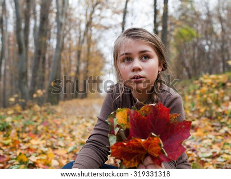 Teenage girl holding bouquet of red and yellow autumn leaves - stock photo