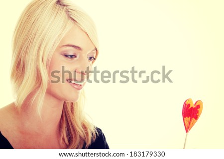 Teenage girl holding red heart shaped lollipop isolated  - stock photo