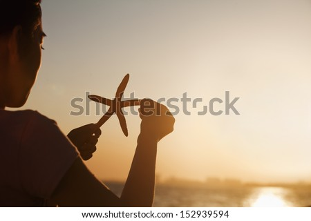 Teenage girl holding up starfish, sunset - stock photo