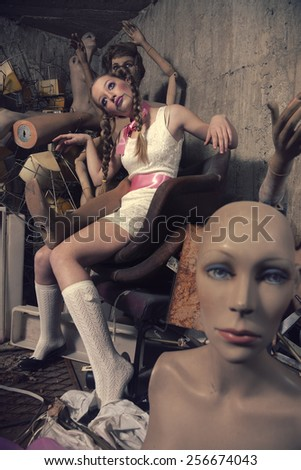 Teenage girl in concrete room full of  mannequin dolls