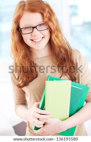 Teenage girl in eyeglasses holding books and looking at camera with smile - stock photo