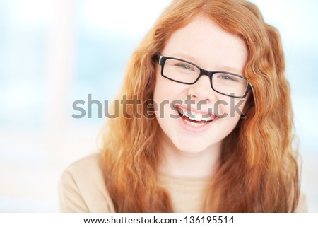 Teenage girl in eyeglasses looking at camera and laughing - stock photo