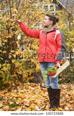 Teenage girl in golden fall foliage - stock photo