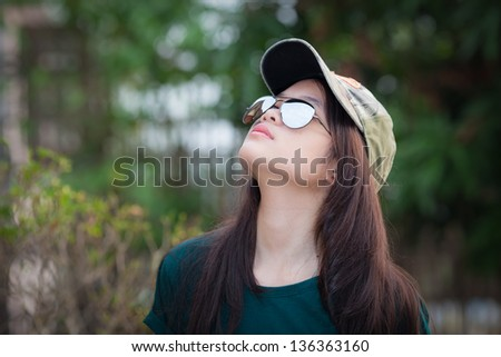 Teenage girl in green tone wear sun glasses looking to the sky - stock photo