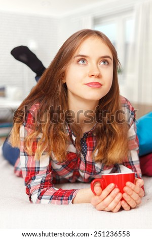 Teenage girl in her room with a cup of coffee