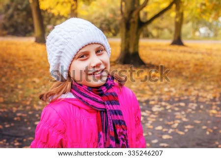 Teenage girl in knitted hat in a Park in autumn
