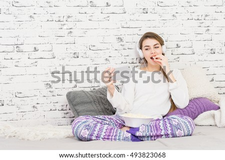 Teenage girl in modern purple and white pajamas at home with smart phone and headphones sitting in bed eating popcorn. Modern minimalist bedroom with brick wall. No retouch.