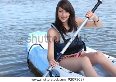 Teenage girl in row boat - stock photo