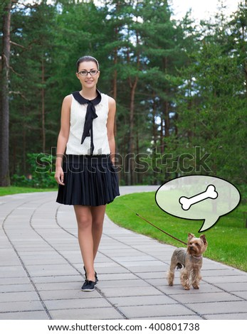 teenage girl in school uniform walking with hungry dog yorkshire terrier in summer park - stock photo