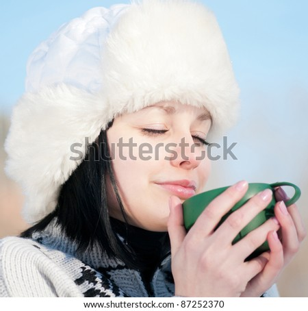 Teenage girl in winter hat with cup of hot drink - stock photo