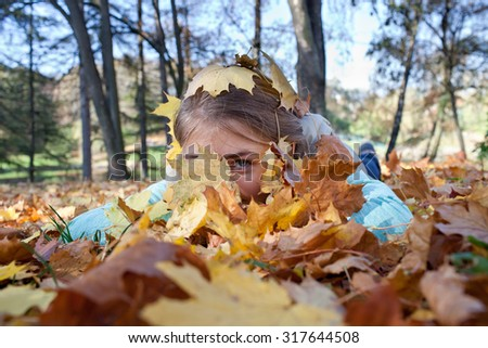 Teenage Girl is lying in the forest beneath the yellow leaves and looking at you with one eye - stock photo