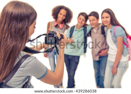 Teenage girl is taking photo of her friends using a camera, isolated on white - stock photo