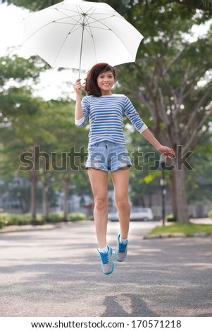 Teenage girl jumping with an umbrella
