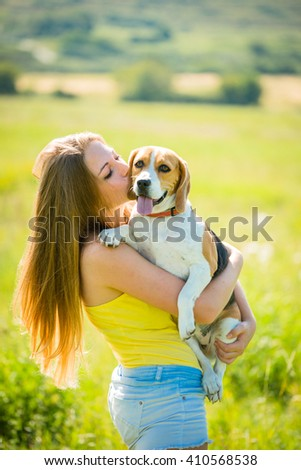 Teenage girl kissing her beagle dog - outdoor in nature - stock photo