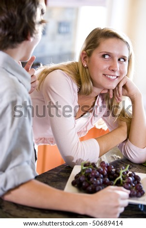 Teenage girl leaning on kitchen counter talking with brother - stock photo